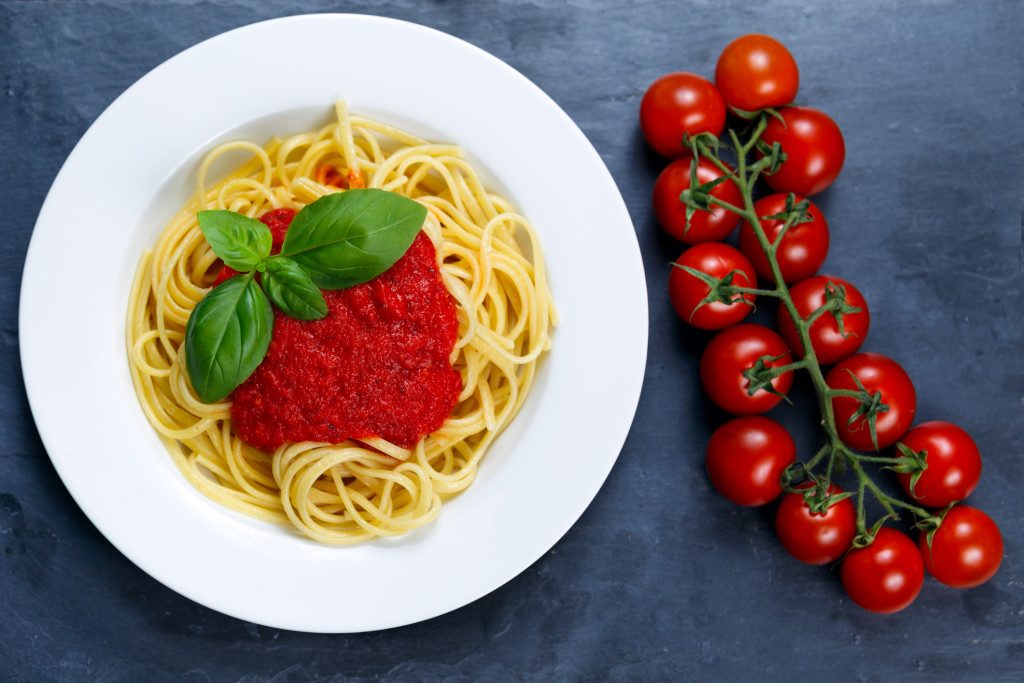 Spaghetti with marinara sauce and basil leaves on top, decorated with cherry tomatoes. on blue background.